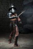 Gladiador no capacete e armadura que guarda a espada Fotografia de Stock Royalty Free