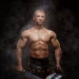 Gladiador que se coloca en un humo en casco y con la espada Fotografía de archivo libre de regalías