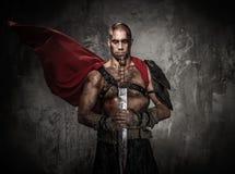 Gladiateur blessé tenant l'épée photographie stock