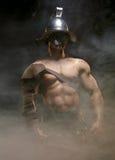 Gladiateur se tenant dans une fumée dans le casque et avec l'épée Photographie stock