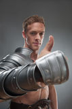 Gladiator in armour pointing at something over Royalty Free Stock Photography