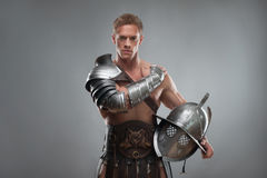Gladiator in armour posing with helmet over grey Stock Images