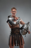 Gladiator in armour posing with helmet over grey stock photo