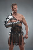 Gladiator in armour posing over grey background Royalty Free Stock Photo