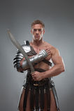 Gladiator in armour posing with sword over grey stock image