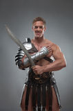 Gladiator in armour posing with sword over grey royalty free stock photo