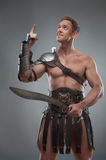 Gladiator in armour posing with sword over grey stock photography