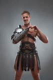 Gladiator in armour showing heart sign over grey royalty free stock photo