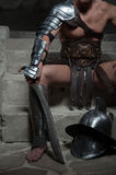 Gladiator in armour sitting on steps of ancient Stock Photography