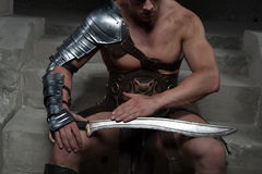 Gladiator in armour sitting on steps of ancient Royalty Free Stock Images