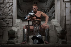 Gladiator in armour sitting on steps of ancient Stock Image