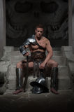 Gladiator in armour sitting on steps of ancient Royalty Free Stock Image