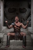 Gladiator in armour sitting on steps of ancient Royalty Free Stock Photography