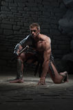 Gladiator with axe kneeling Stock Photo