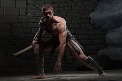 Gladiator with axe kneeling Royalty Free Stock Photos