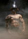 Gladiator, der in einem Rauche im Sturzhelm und mit Klinge steht Stockfotografie