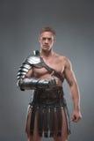 Gladiator in der Rüstung, die über grauem Hintergrund aufwirft Stockfotos