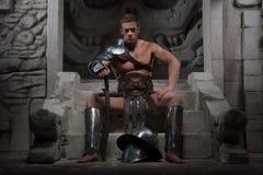 Gladiator in der Rüstung, die auf Schritten von altem sitzt stockbild