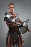 Gladiator in der Rüstung, die mit Sturzhelm über Grau aufwirft Lizenzfreie Stockfotografie