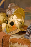 Gladiator helmet. A gladiator helmet resting on a table with animal skins Royalty Free Stock Images