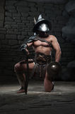 Gladiator in helmet and armour holding sword royalty free stock photo