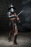 Gladiator in helmet and armour holding sword Royalty Free Stock Photography