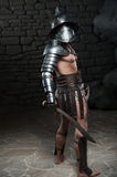 Gladiator in helmet and armour holding sword Stock Photos