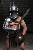 Gladiator im Sturzhelm und Rüstung, die Klinge hält Stockbild