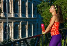 Woman jogger with water bottle relaxing after workout. Gladiator inspiring trainings. stylish woman jogger in sport clothes in Rome, Italy with water bottle stock photography