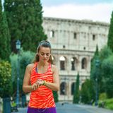 Young woman jogger in Rome, Italy using fitness bracelet Royalty Free Stock Images