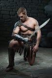 Gladiator med att knäfalla för svärd Arkivbild