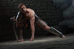 Gladiator med att knäfalla för svärd Royaltyfria Bilder