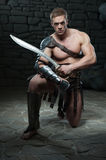 Gladiator with sword kneeling stock image