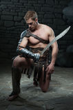 Gladiator with sword kneeling Stock Photography