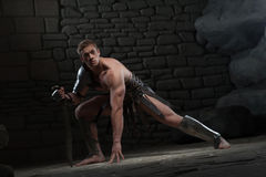 Gladiator with sword kneeling Royalty Free Stock Photo