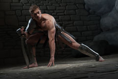 Gladiator with sword kneeling Royalty Free Stock Images