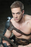 Gladiator with sword kneeling Stock Photo