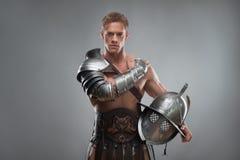 Gladiator w zbroi pozuje z hełmem nad popielatym Obrazy Stock