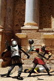 Gladiators fighting. Two gladiators fighting into a coliseum. Another gladiator is lying on the ground with blood in his body royalty free illustration