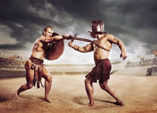 Gladiators fighting on the arena of the Colosseum. Rome Gladiators fighting with swords on the arena of the Colosseum stock image