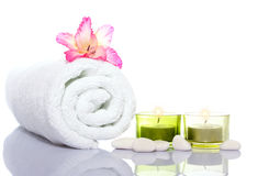 Gladiola,white towel,candles and white river stones Stock Photos