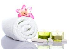 Gladiola, witte handdoek, kaarsen en witte rivierstenen stock foto's