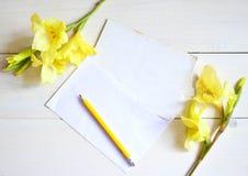 Gladiolo y tarjeta amarillos con el lápiz en fondo de madera foto de archivo libre de regalías