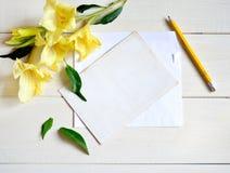 Gladiolo y tarjeta amarillos con el lápiz en fondo de madera imagen de archivo