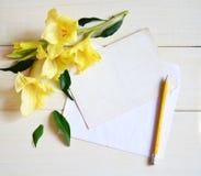 Gladiolo y tarjeta amarillos con el lápiz en fondo de madera imagenes de archivo