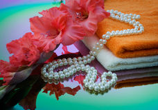 Gladiolus, towel and pearls. Are reflected in the color mirror Royalty Free Stock Image