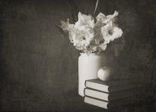 Gladioluses in einem weißen Krug mit Büchern und Apfel Stockbilder