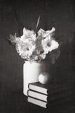 Gladioluses in einem weißen Krug mit Büchern und Apfel Stockfotografie