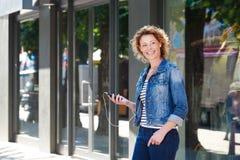 Gladlynt äldre kvinna som går med mobiltelefonen i stad arkivfoto