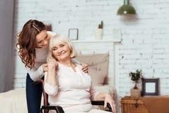 Gladlynt äldre kvinnasittig i rullstolen Royaltyfri Bild